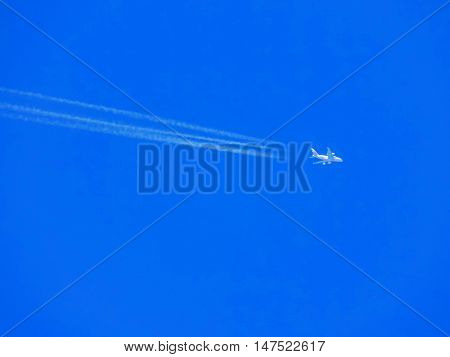 Airplane with chemtrails on blue sky during day