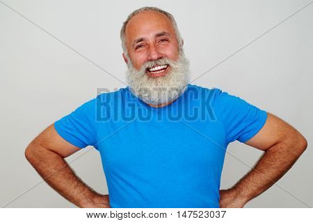 Handsome aged man in blue T-shirt is standing with hands on hips and smiling against white background