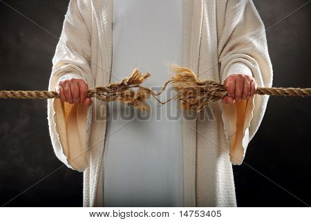 Jesus hands holding frayed rope over dark background