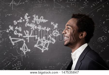 Portrait of smiling African American man standing near blackboard with formulas on it. Concept of engineering and exact sciences education.