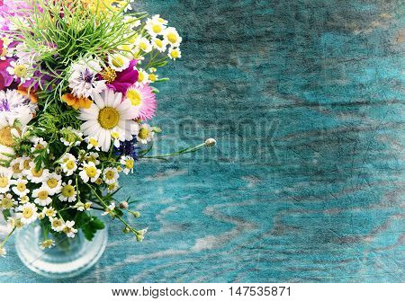 Bouquet of fresh summer flowers on the blue wooden grunge desk. Mock up for greeting cards, holiday postcards, invintation and anniversary celebration in vintage hipster style with copy space