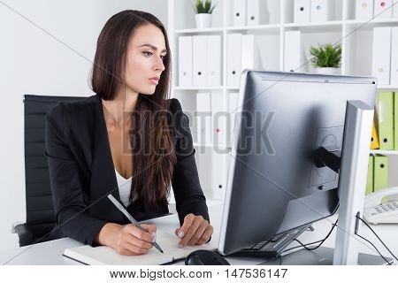 Serious Businesswoman With Long Hair Taking Notes