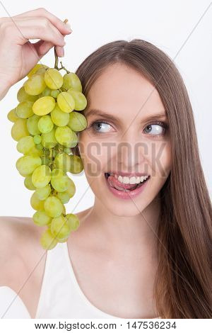 Woman With Stuck Out Tongue And Grapes