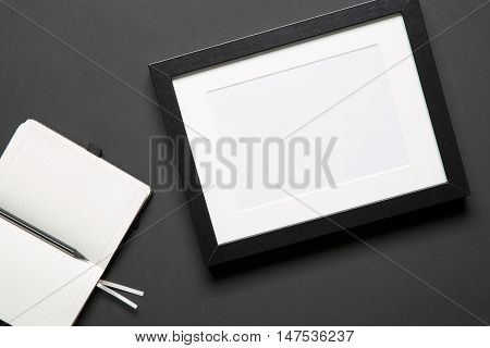 Top view of photo frame an open notebook and a sharp pencil. Concept of sketching and making a work of art