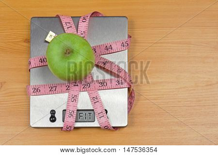 Green apple on digital kitchen scale wrapped in tape measure with fit sign on display