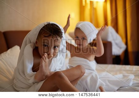 Child after bath. Cute little girl with wet curly hair wearing a bathrobe and head towel sitting on a white bed using lotion and brush. Hygiene for kids. Bathroom textile for babies and children.