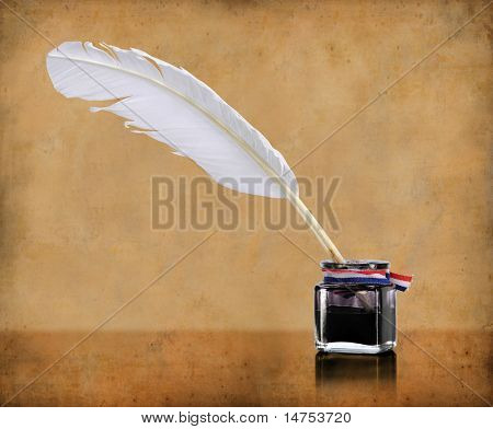 Vintage writing quill and inkwell over grunge background
