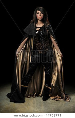 Female vampire standing over dark background with spotlight