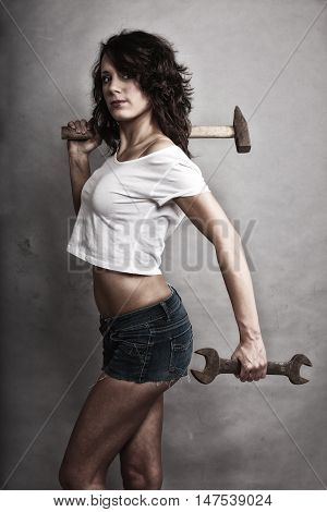 Sex equality and feminism. Sexy girl holding hammer and wrench spanner tools. Attractive woman working as repairman.