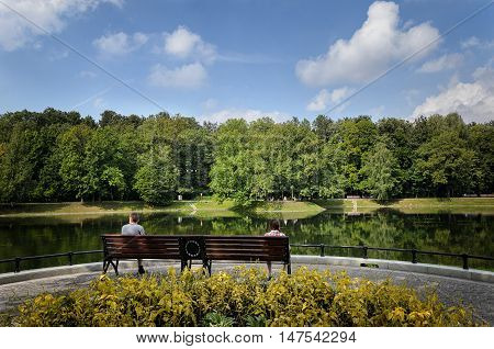 People sit on a bench and look at the beautiful pond in the park sit on a bench and look at the pond