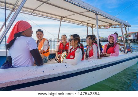 Semporna,Sabah-Sept 10,2016:Happy Asian tourists on the boat at the Semporna jetty.Semporna is a gateway for diving & snorkeling trips to the islands of Sipadan,Mabul,Mataking,Maiga & others