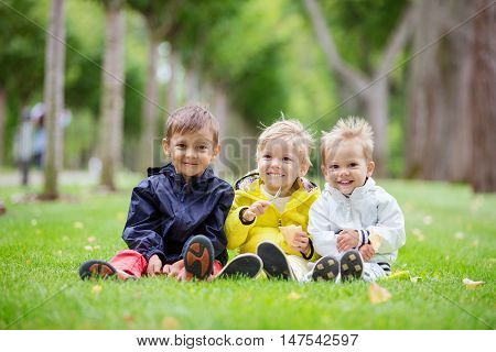 Three young boys sitting on the grass in a park and smiling, the boy in the middle eating ice cream