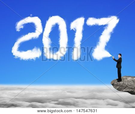 Businessman spraying white 2017 year cloud shape in blue sky cloudscape background