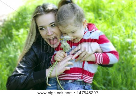Mother and five year old daughter playing in the park in the spring afternoon