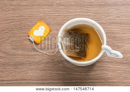 Cup of tea with tea bag on wooden background