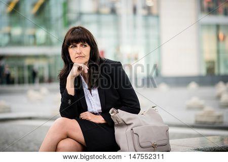 Portrait of senior business woman sitting in street hand under chin