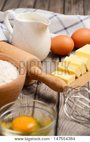 Ingredients for baking - milk, butter, eggs and flour. Rustic background, selective focus.