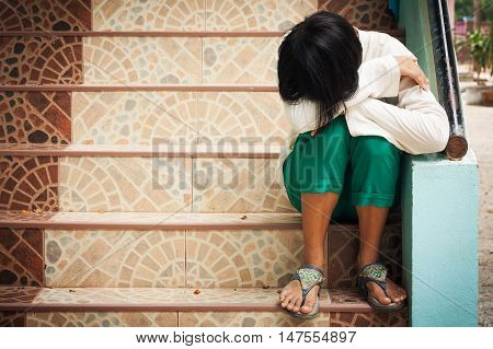 girl sitting alone at staircase in the park