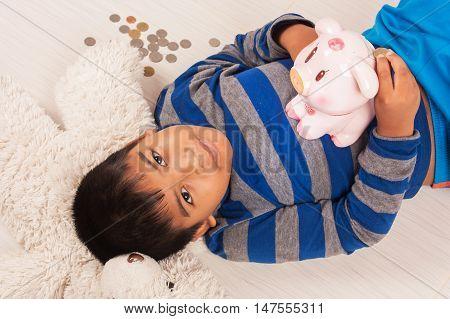 cute asian boy saving money in piggybank