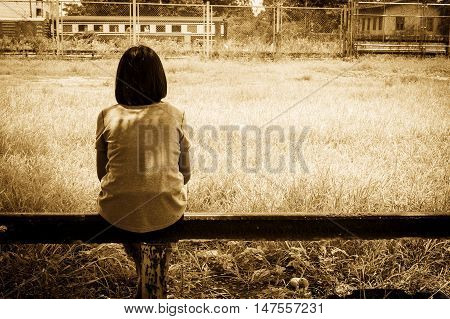 sad asian girl sitting alone near railway Stations vintage tone