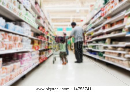 blurry of father and son walk shopping in the supermarket