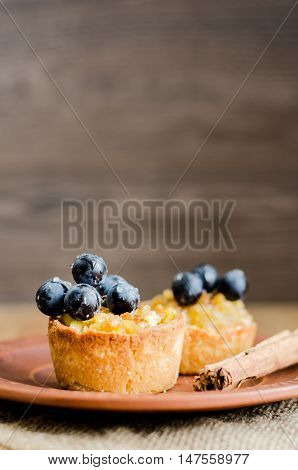 tartlets with apple, grapes and cinnamon on wooden background, selective focus