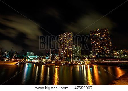 Beautiful view of Ala Wai Harbor the largest yacht harbor of Hawaii at night. Honolulu Harbor skyline reflecting in the water. Oahu in Hawaii United States.