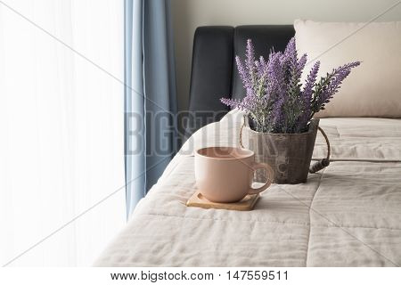 The bed with lavender flower and coffee cup in the morning Selected focus on flower pot.