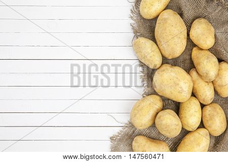 Raw potatoes isolated on a white wooden background top view