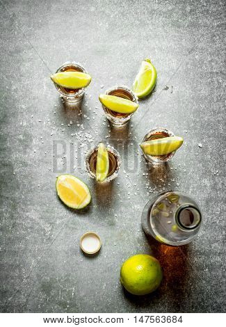 bottle of tequila with lime and salt. On the stone table.