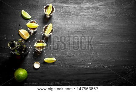 bottle of tequila with shot glasses, fresh lime and salt. On the chalkboard.