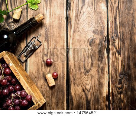 Red wine with a box of grapes and a corkscrew. On a wooden table.