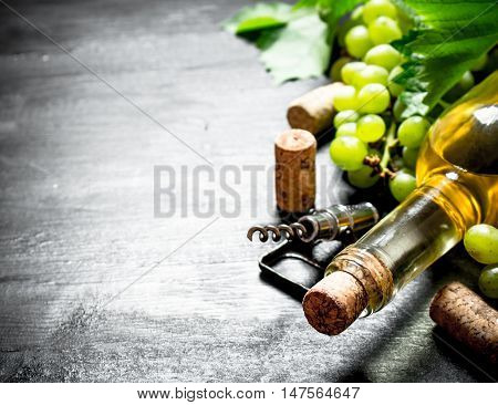 bottle of white wine with a corkscrew. On a black wooden background.