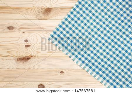 Blue checkered towel over wooden kitchen table. View from above
