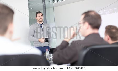 Relaxed cheerful team leader and business owner leading informal in-house business meeting. Business and entrepreneurship concept.
