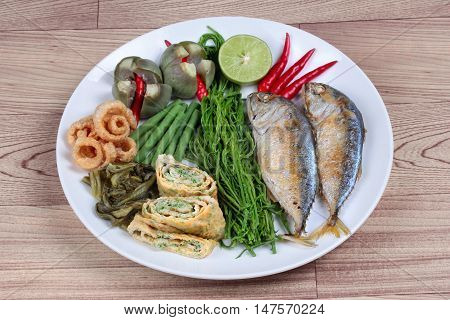 Ready side dish of deep fired mackarel,vegetable omelet,crispy pork rind,pickle lettuce,halve green lemon,red chili and boiled of eggplant,lentils,acacia  on wood. Side view
