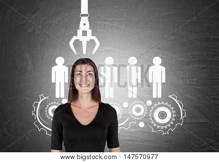 Smiling girl in black standing against chalkboard with conveyor belt of people. Concept of HR policy and the right candidate picking.