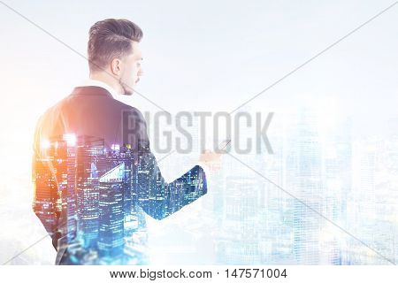 Side view of businessman with smart phone standing against big city panorama. Concept of international corporation. Toned image. Double exposure.