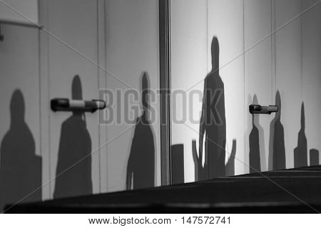 Abstract silhouettes of people at business meeting, Seminar event room with dark shadows in background. Leaders in the background business or policy concept. Black and white image.
