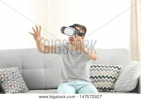 Young man wearing virtual reality glasses and sitting on sofa in a room
