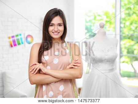 Pretty young dressmaker with measuring tape