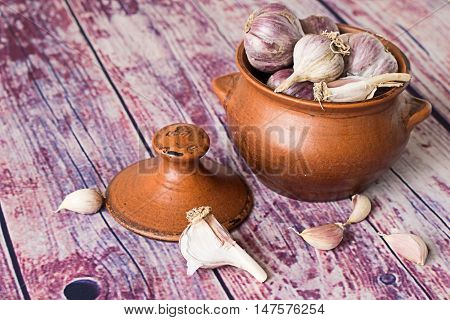Heads of garlic in a clay pot and garlic cloves on an old wooden table.