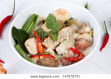 Close up focus of chicken and galangal in coconut milk soup and herb on white background.