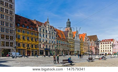 WROCLAW, POLAND - MARCH 19, 2016: Tourists and locals walk in the area of the 13th century Main Market Square, one of the largest markets in Europe with the largest two town halls in Poland.