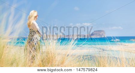 Relaxed woman wrapped in colorful scarf, enjoying sun, freedom and life at beautiful Balos beach in Greece. Concept of holidays, vacations, freedom, joy and well being.