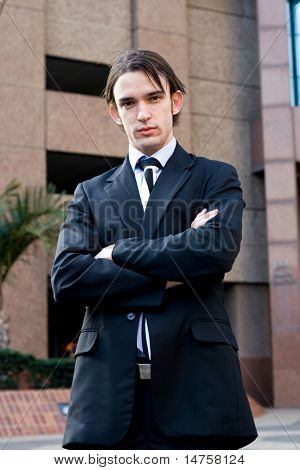 businessman standing in front of a corporate building