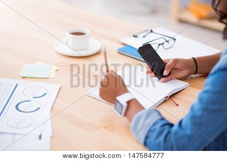 Involved in project. Pleasant woman sitting at the table and using cell phone while working