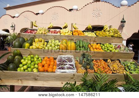 Exotic fruit stall outdoors on sunny day by pink building in market