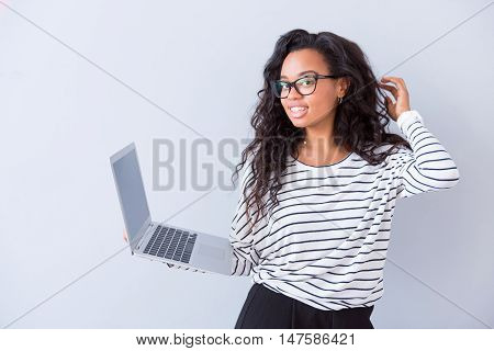 In pace with time. Positive delighted woman holding laptop and expressing gladness while standing isolated on white background