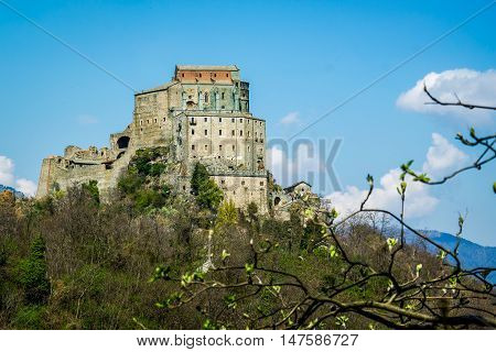 Sacra di San Michele church seen from a hill near herthe church is located atop a rocky crag base and towers above the valley.It is located near Turin Italy